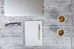 Tabla del escritorio de oficina con el ordenador portátil y otras fuentes con la taza de café Imagen de archivo libre de regalías