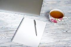 Tabla del escritorio de oficina con el ordenador portátil y otras fuentes con la taza de té Fotografía de archivo libre de regalías