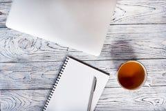 Tabla del escritorio de oficina con el ordenador portátil y otras fuentes con la taza de té Foto de archivo libre de regalías