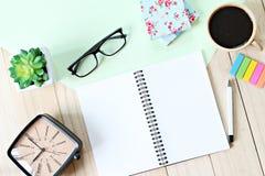 Tabla del escritorio de oficina con el papel del cuaderno, los accesorios y la taza de café abiertos Imagenes de archivo