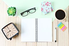 Tabla del escritorio de oficina con el papel del cuaderno, los accesorios y la taza de café abiertos Fotografía de archivo libre de regalías