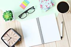Tabla del escritorio de oficina con el papel del cuaderno, los accesorios y la taza de café abiertos Imágenes de archivo libres de regalías