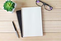 Tabla del escritorio de oficina con el papel, la pluma y las lentes abiertos del cuaderno Fotos de archivo