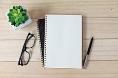 Tabla del escritorio de oficina con el papel, la pluma y las lentes abiertos del cuaderno Fotos de archivo libres de regalías
