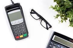 Tabla del escritorio de oficina con el terminal y la calculadora del pago Foto de archivo
