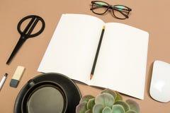 Tabla del escritorio de oficina con la taza de café de los vidrios de las tijeras del cuaderno suculenta y el lápiz Mofa encima d imagen de archivo