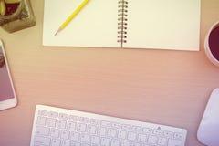 Tabla del escritorio de oficina con la taza del ordenador, del cuaderno, de la flor y de café Endecha plana Imagen de archivo libre de regalías