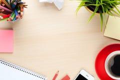 Tabla del escritorio de oficina con las fuentes, la taza de café y la flor Imagen de archivo