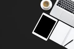 Tabla del escritorio del trabajo del negro de la oficina con el ordenador portátil, la tableta, la taza de café y el cuaderno en  Imágenes de archivo libres de regalías