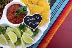 Tabla del partido de Cinco de Mayo con el disco de la comida Imagen de archivo