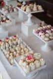 Tabla del postre de la recepción nupcial con c blanca adornada deliciosa Imagen de archivo libre de regalías