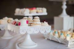 Tabla del postre de la recepción nupcial con c blanca adornada deliciosa Foto de archivo