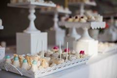 Tabla del postre de la recepción nupcial con c blanca adornada deliciosa Fotografía de archivo