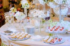 Tabla del postre en la ceremonia de boda Macarrones, torta, merengue Imágenes de archivo libres de regalías
