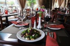 Tabla del restaurante con la ensalada y el vino servidos Foto de archivo