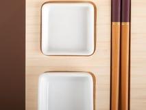 Tabla del sushi con las placas y los palillos Fotos de archivo libres de regalías