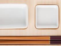 Tabla del sushi con las placas y los palillos Imágenes de archivo libres de regalías