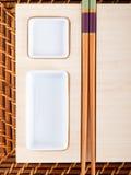 Tabla del sushi con las placas y los palillos Imagen de archivo