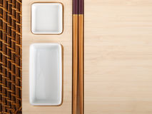 Tabla del sushi con las placas y los palillos Imagenes de archivo