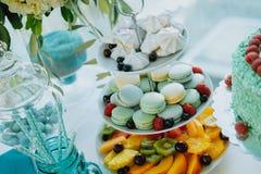 Tabla dulce con los macarrones, las frutas y la torta coloridos imagen de archivo libre de regalías