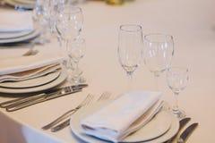 Tabla elegante con las placas vacías, vidrios, cubiertos, servilleta blanca en la recepción nupcial Abastecimiento de lujo y porc foto de archivo