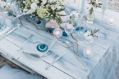 Tabla elegante puesta en los pasteles azules para una boda de playa imagenes de archivo
