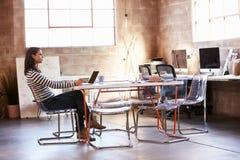 Tabla femenina de Sitting At Meeting del diseñador que trabaja en el ordenador portátil imagen de archivo libre de regalías
