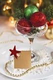 Tabla festiva adornada con las bolas y la tarjeta de la Navidad para los wi Imagen de archivo
