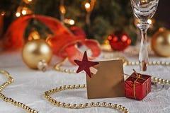 Tabla festiva adornada con las bolas y la tarjeta de la Navidad para los wi Fotos de archivo libres de regalías