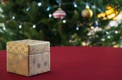 Tabla festiva con una caja de regalo y un árbol de navidad adornado en fondo Fotos de archivo