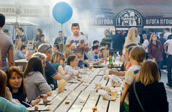 Tabla grande al aire libre con la gente de consumición y de consumición durante festival popular de la comida de la calle Foto de archivo libre de regalías