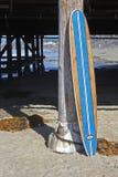 Tabla hawaiana de madera contra el embarcadero de la playa de California Fotografía de archivo libre de regalías