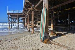Tabla hawaiana de madera contra el embarcadero de la playa de California Imagenes de archivo