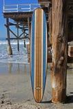 Tabla hawaiana de madera contra el embarcadero de la playa de California Fotos de archivo