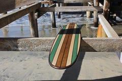 Tabla hawaiana de madera contra el embarcadero de la playa de California Imagen de archivo