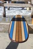 Tabla hawaiana de madera contra el embarcadero de la playa de California Imagen de archivo libre de regalías
