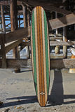 Tabla hawaiana de madera contra el embarcadero de la playa de California Fotografía de archivo