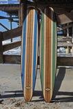 Tabla hawaiana de madera contra el embarcadero de la playa de California Foto de archivo