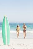 Tabla hawaiana en la arena y dos mujeres que corren en la playa Imágenes de archivo libres de regalías