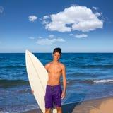 Tabla hawaiana que agujerea feliz de la persona que practica surf adolescente del muchacho en la playa Fotos de archivo