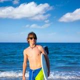 Tabla hawaiana que agujerea feliz de la persona que practica surf adolescente del muchacho en la playa Fotografía de archivo libre de regalías