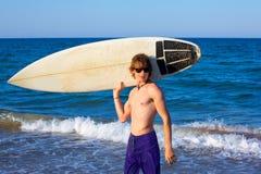 Tabla hawaiana que agujerea feliz de la persona que practica surf adolescente del muchacho en la playa Imagen de archivo libre de regalías