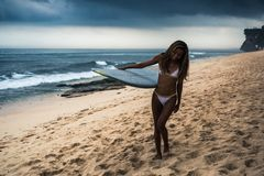 Tabla hawaiana que lleva de la mujer en la playa Foto de archivo
