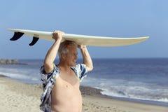 Tabla hawaiana que lleva de la persona que practica surf de sexo masculino Fotos de archivo libres de regalías