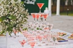 Tabla hermosa del día de fiesta con bocados y una pirámide de vidrios Foto de archivo libre de regalías