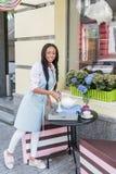 Tabla joven sonriente de la porción de la camarera en café al aire libre Foto de archivo