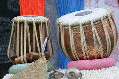 Tabla and karatalas against the backdrop of colorful scarves. Stock Image