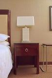 Tabla lateral con la lámpara de mesa entre la cama y la tabla Foto de archivo libre de regalías