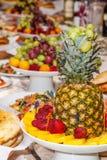 Tabla lujosamente adornada con las frutas tropicales, las fresas, el pan y la piña Fotos de archivo libres de regalías