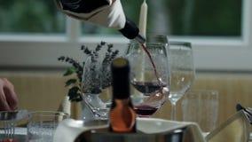 tabla maravillosamente preparada para la cena y el camarero en los cuales está vertiendo el vino rojo almacen de metraje de vídeo